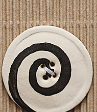 1 Large white button with black swirl